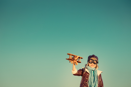 innovation concept: Kid pilot with toy wooden airplane against autumn sky background. Happy child playing outdoors. Retro toned