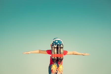 lider: Cabrito con el jet pack contra fondo del cielo de otoño. Niño que juega al aire libre. Éxito, líder y ganador concepto. Retro tonificado