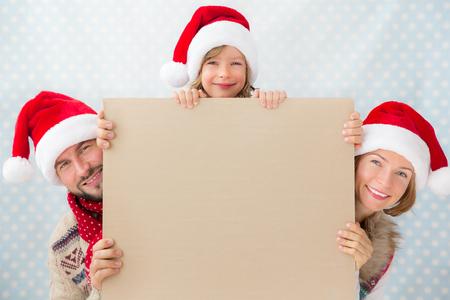 familia: La familia feliz que sostiene la tarjeta de Navidad. Concepto de vacaciones de Navidad