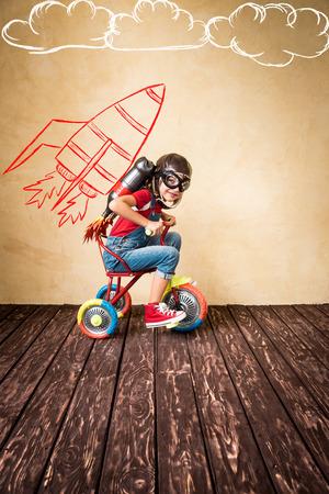 Kid met jet pack paardrijden fiets. Kind spelen thuis. Succes, leider en winnaar begrip