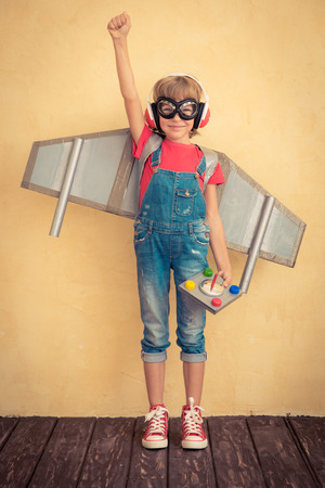 leader concept: Happy child playing with toy jetpack at home. Success and leader concept