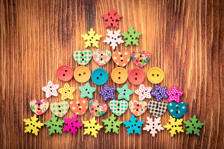 xmas background: Christmas tree of buttons on wood background. Xmas holiday concept