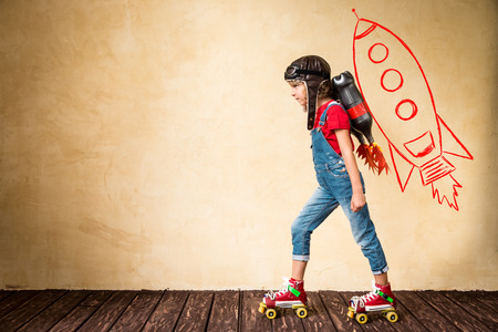 roller skates: Kid with jet pack riding on roller skates. Child playing at home. Success, leader and winner concept