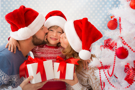 xmas tree: Happy family holding Christmas gifts near Xmas tree. Child, mother and father having fun at home Stock Photo