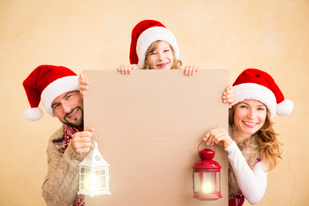 Happy family holding Christmas banner blank. Xmas holiday concept Stock Photo