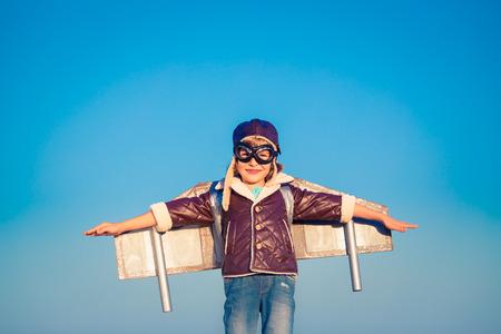 푸른 겨울 하늘 배경에 장난감 제트 팩 아이가 조종사. 야외에서 놀고있는 행복한 아이
