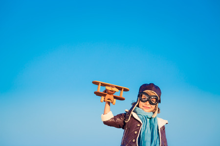 innovation concept: Kid pilot with toy wooden airplane against blue winter sky background. Happy child playing outdoors