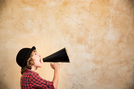 Kid skrika genom vintage megafon. Kommunikationskoncept. Retrostil Stockfoto