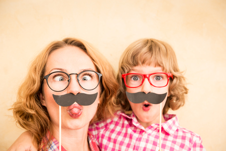 girl glasses: Mother and child with fake mustache. Happy family playing in home Stock Photo