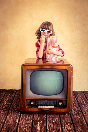 retro tv: Child playing at home. Funny kid eating popcorn on retro TV. Cinema concept