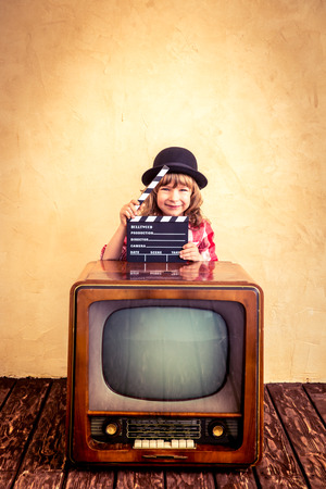 camera girl: Child playing at home. Funny girl holding clapper board. Retro TV. Cinema concept Stock Photo