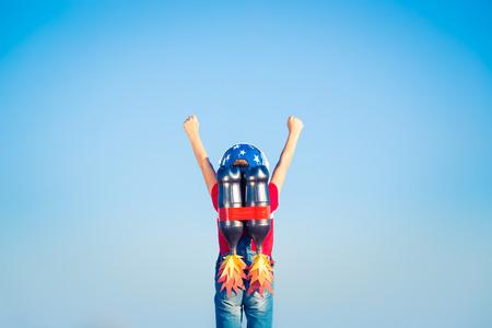 Cabrito con el jet pack contra el cielo azul. Niño que juega al aire libre. Éxito, líder y ganador concepto