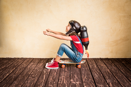 Kid with jet pack riding on skateboard. Child playing at home. Success, leader and winner concept