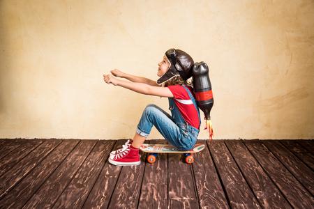 imaginacion: Cabrito con el jet pack montar en monopatín. Niño que juega en casa. Éxito, líder y ganador concepto Foto de archivo