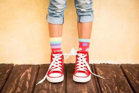 pies: Zapatillas de deporte rojas en las piernas de los niños