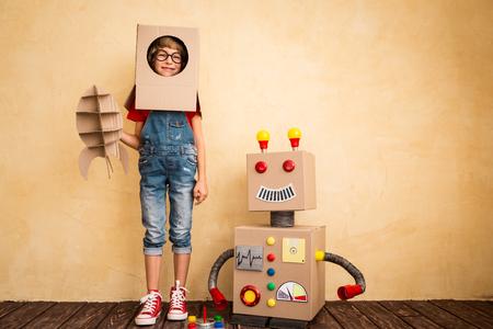 Gelukkig kind spelen met speelgoed robot thuis. Innovatie technologie en succes concept