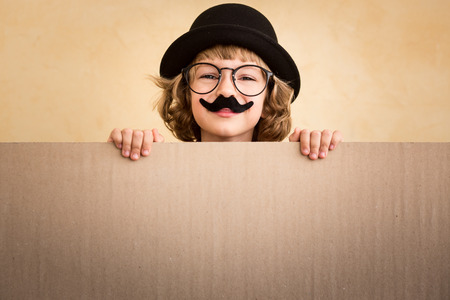 Funny kid with fake mustache holding banner blank