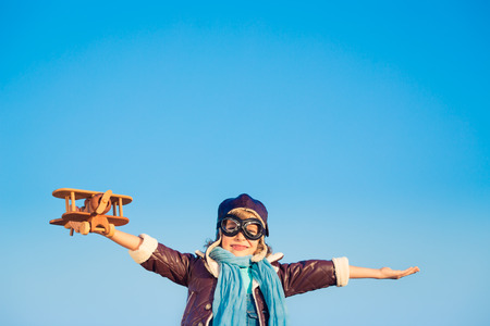 Kid pilot with toy wooden airplane against blue winter sky background. Happy child playing outdoors Stock Photo - 46594286