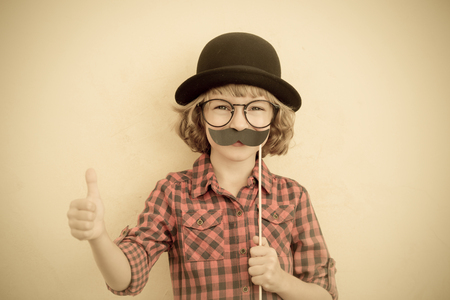ni�os jugando: Funny kid with fake mustache. Happy child playing in home Foto de archivo