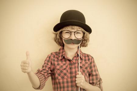 Grappige jongen met valse snor. Gelukkig kind spelen in huis Stockfoto