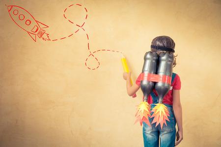 enfants: Kid avec jet pack dessiner le croquis sur le mur. Enfant jouant � la maison. Succ�s, leader et le concept de gagnant