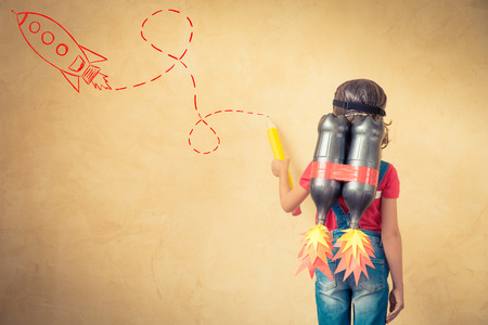 Dzieci: Kid with jet pack draw sketch on wall. Child playing at home. Success, leader and winner concept