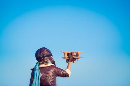 pilotos aviadores: Piloto Kid con avión de juguete de madera contra el fondo del cielo azul de invierno. Niño feliz jugando al aire libre