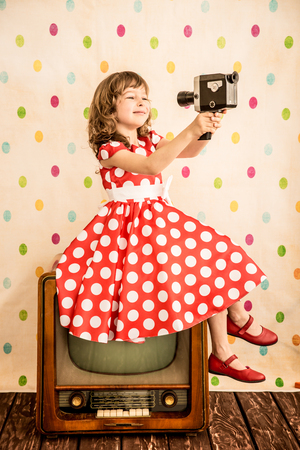 Child playing at home. Girl holding retro camera. Cinema concept