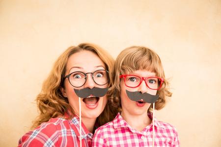 Madre y niño con bigote falso. Juego de la familia feliz en el hogar Foto de archivo - 46594231