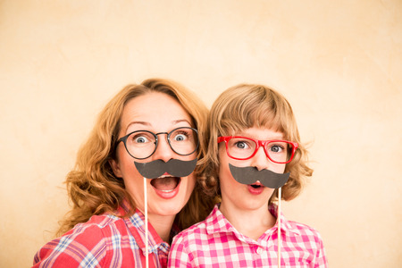 mom: Mother and child with fake mustache. Happy family playing in home Stock Photo