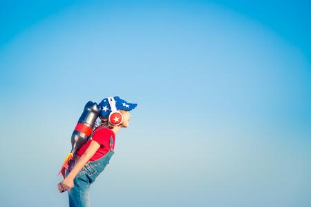 cohetes: Cabrito con el jet pack contra el cielo azul. Niño que juega al aire libre. Éxito, líder y ganador concepto