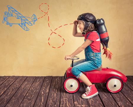 enfants: Kid avec jet pack conduisait la voiture de jouet rétro. Enfant jouant à la maison. Succès, leader et le concept de gagnant