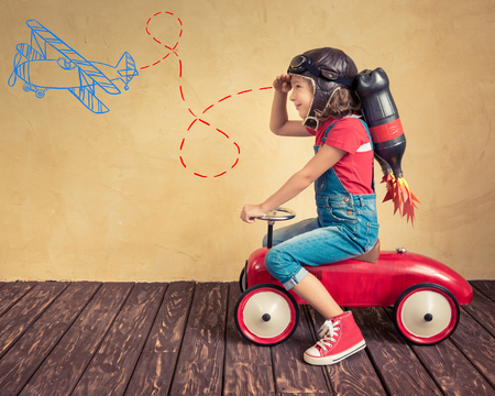 Kid with jet pack driving retro toy car. Child playing at home. Success, leader and winner concept