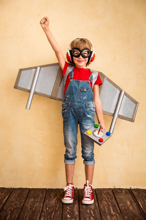 Kid pilot playing with toy jetpack at home. Success and leader concept Stock Photo