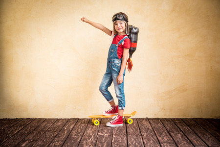 superman: Kid with jet pack riding on skateboard. Child playing at home. Success, leader and winner concept