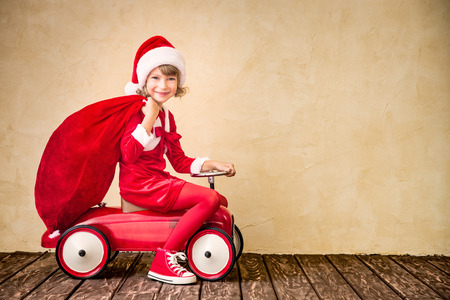Child riding in red car. Kid holding Christmas bag. Xmas holiday concept Foto de archivo