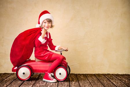 Paseos a Niño en coche rojo. Kid celebración de la bolsa de Navidad. Concepto de vacaciones de Navidad Foto de archivo - 47210577
