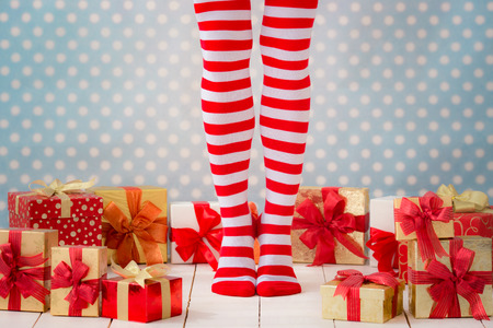 Sexy Santa woman legs. Christmas shopping concept. Xmas gift box Stock Photo