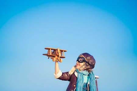 Kid Pilot mit Spielzeug aus Holz Flugzeug gegen blauen Winterhimmel Hintergrund. Glückliches Kind im Freien spielen Lizenzfreie Bilder