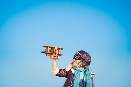 Kid pilot with toy wooden airplane against blue winter sky background. Happy child playing outdoors