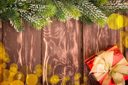 xmas background: Christmas tree branch and gift box on wood background. Xmas holiday concept