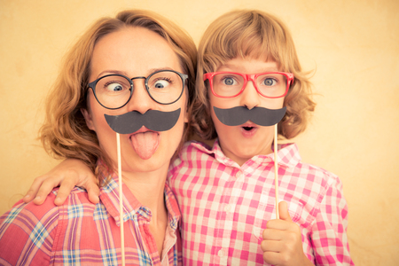 family playing: Mother and child with fake mustache. Happy family playing in home Stock Photo