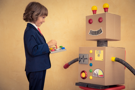 innovation concept: Portrait of young businessman with toy robot in modern loft office. Success, creative and innovation technology concept. Copy space for your text