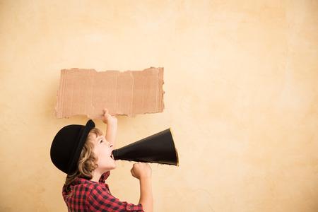 loudspeaker: Kid shouting through vintage megaphone. Communication concept. Retro style