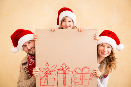 christmas poster: Happy family holding Christmas poster blank. Xmas holiday concept