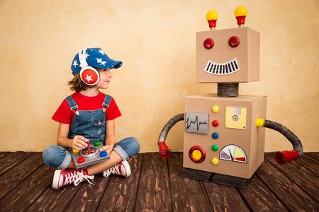 juguete: Ni�o feliz que juega con el robot de juguete en casa. Retro tonificado Foto de archivo