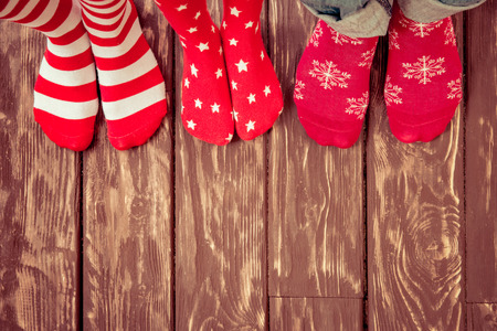 sock: Feet wearing Christmas socks on wood floor. Happy family at home. Xmas holidays concept