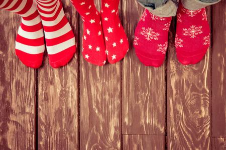 Pies llevaba calcetines de Navidad en el piso de madera. Familia feliz en el hogar. Navidad concepto de vacaciones Foto de archivo