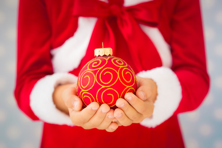 miracle tree: Child holding Christmas ball. Xmas holiday concept