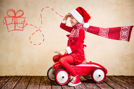 Child ride in red Christmas car. Xmas holiday concept
